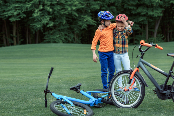 2 children with helmets on standing by bicycles