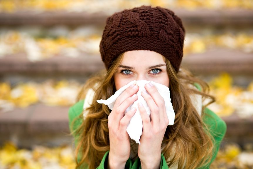 woman in woolly hat blowing her nose